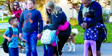 April and Rubin Doster, along with their 11-year-old daughter Mya, second from left, greet their other children, from left: Derek, 5, Savannah, 8 and Hailey, 7, after they get off of the school bus in their Palmyra neighborhood on Tuesday, Nov. 5, 2019.