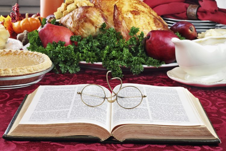 Open Bible with glasses lying on a holiday dinner table with prepared turkey and fixings in background.